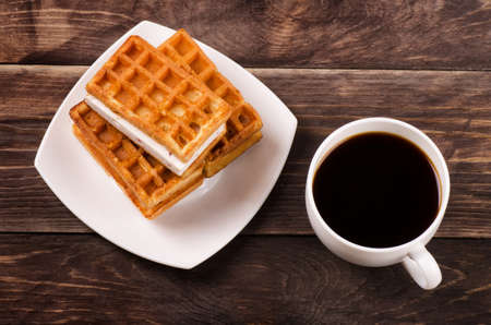 Black coffee and viennese waffles on wooden table