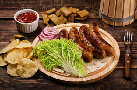 Sausages with beer and crackers on a wooden background  Stock Photo