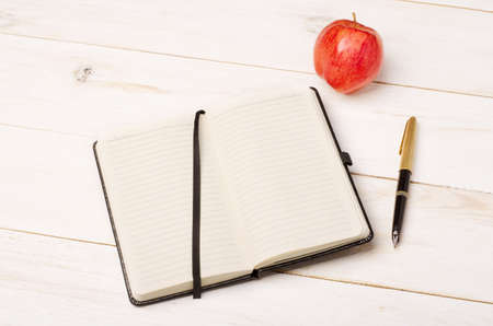 Diary, apple and pen on rustic wooden table Stock Photo