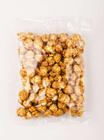 Caramel popcorn in the plastic package on a white background