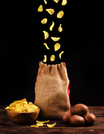 Potato chips fall into a canvas bag isolated on a black background. Flying chips closeup. Stock Photo