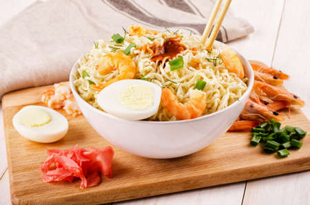 Chinese noodles with shrimp, spring onion and sliced eggs in soy sauce in bowl on cutting board  Stock Photo