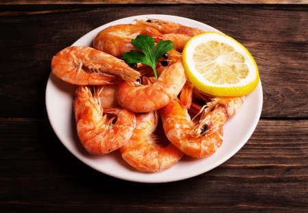Prepared shrimp with lemon and parsley on a white plate on wooden background