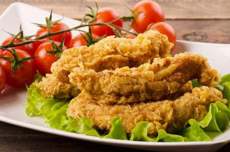Tiras de pollo frito dorado en empanizado con ensalada y tomates en una placa blanca.