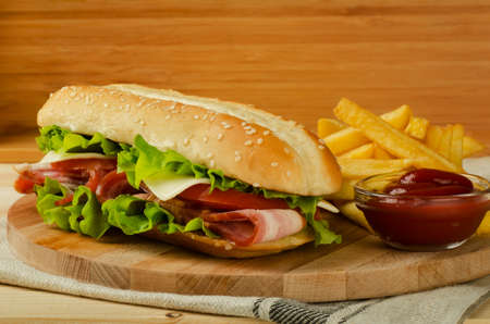 Fresh submarine sandwich with cheese, bacon, tomatoes and lettuce, on light wooden background 写真素材