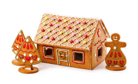 Homemade gingerbread house with Christmas tree and snowwoman isolated on a white background Stock Photo