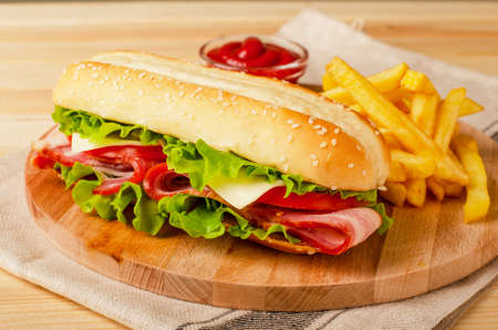 Submarine sandwich with bacon, cheese, tomatoes and lettuce on wooden background
