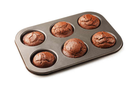 Yummy homemade chocolate muffins in baking pan isolated on a white background