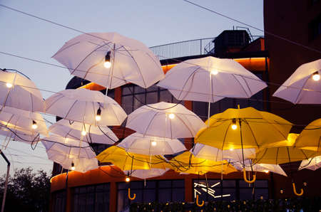 City street decorated with umbrellas and lights. Architecture exterior design in the evening.