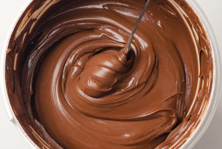 Background of chocolate paste with spoon in a basket