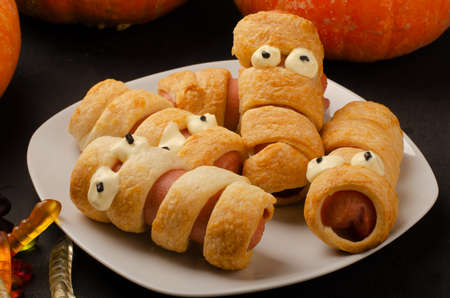 Scary sausage mummies in dough with funny eyes on table. Funny decoration. Halloween food. Stok Fotoğraf