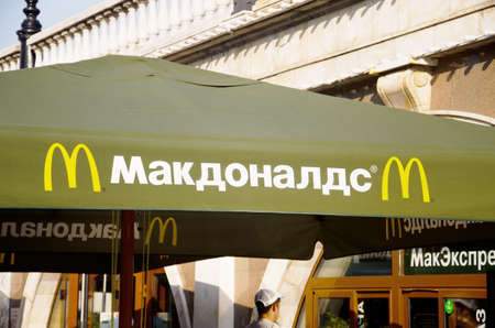 Moscow, Russia - March 7, 2019: McDonald's Restaurant sign on an umbrella on Russian language. McDonald's is an American hamburger and fast food restaurant chain.