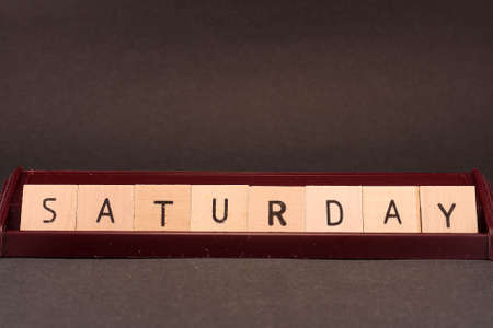 The word Saturday spelled out in wooden tiles