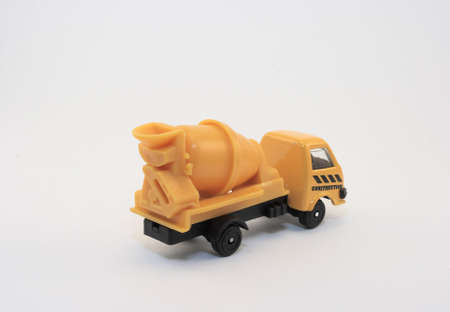 Macro of a yellow toy cement mixer truck presented on a white background photo