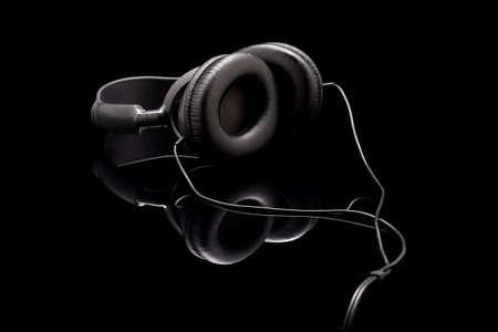 black headphones on black acrylic background
