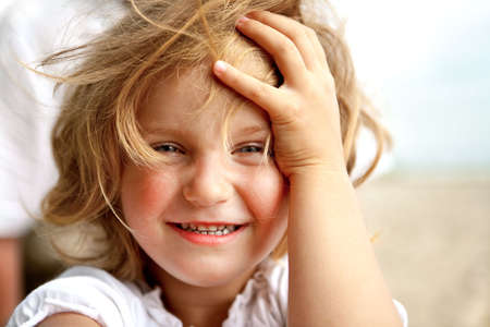 girl with blue eyes smiling and looking straight to the camera Stock Photo