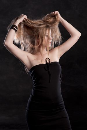 young woman with long hair - hair in hands above head, eyes closed Stock Photo