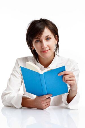 young woman with blue eyes reading a book, looking and smiling, on white background Stock Photo - 6601485