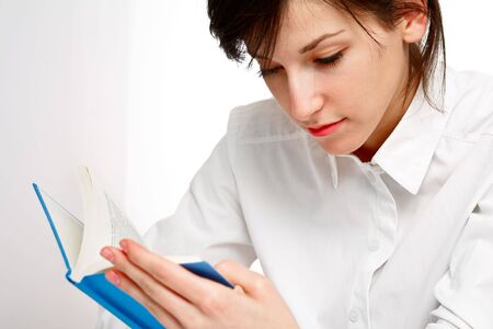 young woman reading with attention, on white background Stock Photo - 6601450