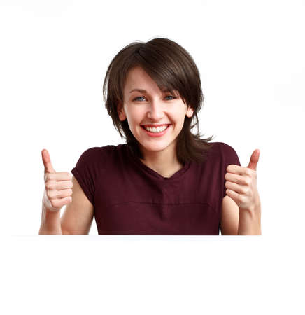 beautiful, happy girl behind an empty sheet of paper showing OK with both hands Stock Photo - 6680011
