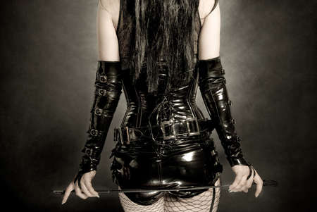 dominating: woman in black latex corset, with horsewhip in hands Stock Photo