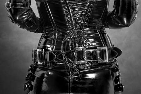 black shiny latex corset with some buckles and ropes Stock Photo