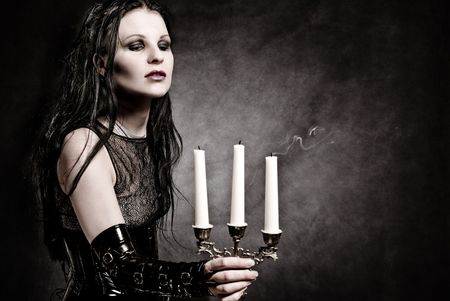 fetish wear: gothic girl in fetish clothes with candles