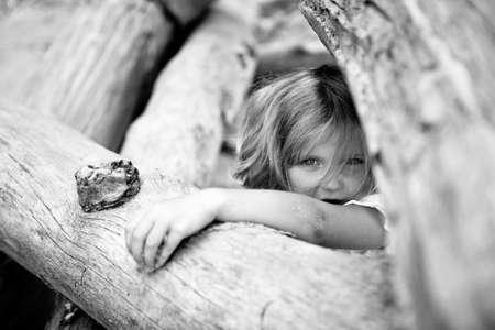 little girl hidden between fallen trees, black and white