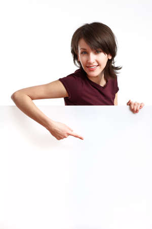 beautiful girl holding an empty white board and pointing her finger down Stock Photo