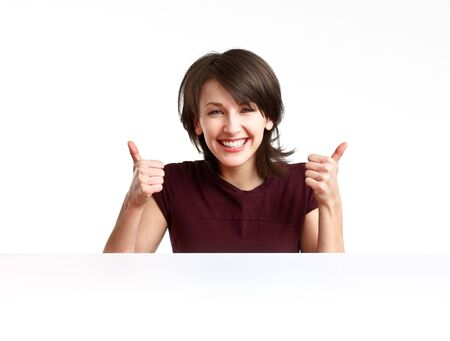 cheerful girl showing OK with both hands behind an empty white board  photo