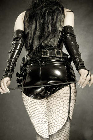 woman in black latex uniform, shorts and corset, with horsewhip in hands