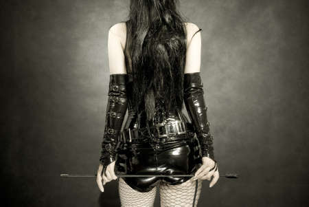 woman in black latex uniform with horsewhip in hands, back photo