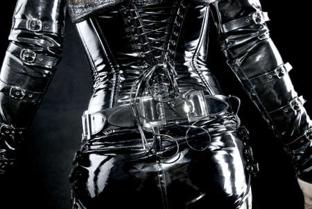 latex: woman in black latex uniform, corset, back