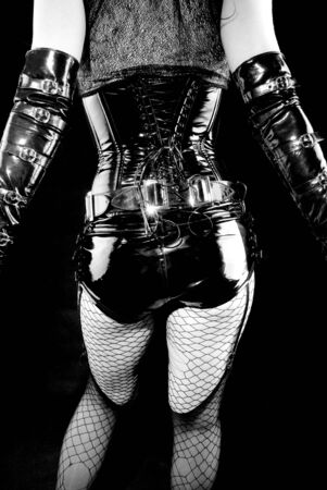 woman in black latex uniform and fishnets, back photo