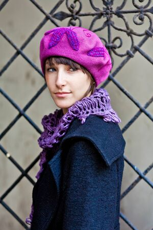 fashionable young woman wearing pink beret and violet scarf