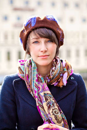 fashionable young woman wearing brown beret and colorful scarf