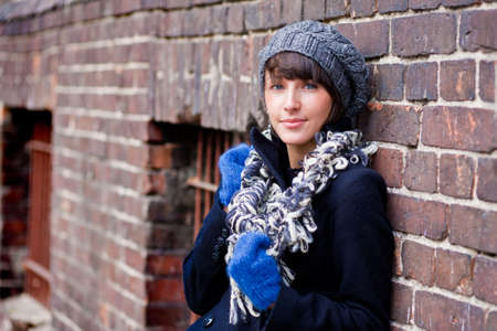 fashionable young woman wearing grey beret, blue gloves and grey scarf Stock Photo