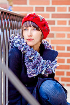 fashionable young woman wearing red beret and blue scarf
