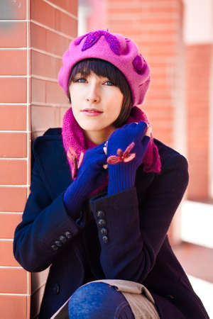 fashionable young woman wearing pink beret, scarf, and blue gloves