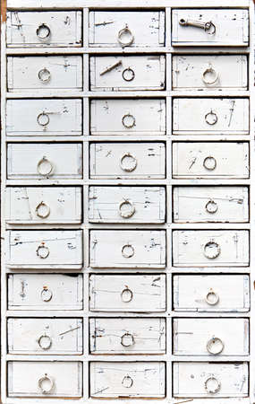 an old, ancient wooden chest of drawers, painted white photo