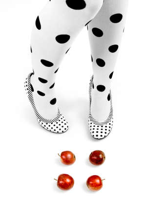 legs, dotted tights and shoes, and red apples. metaphorical: diet and shape  Stock Photo