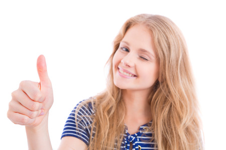 sharpness: beautiful, happy blond girl showing OK - thumb up - with one hand, sharpness on hand, isolated Stock Photo