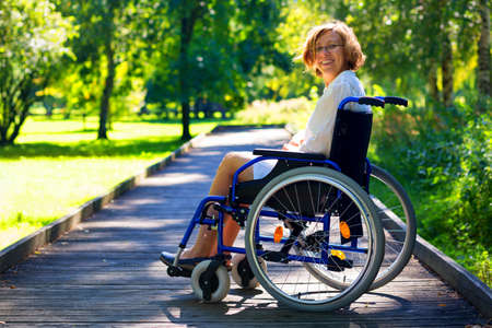 young adult woman: happy young adult woman on wheelchair in the park Stock Photo