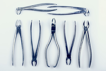 pincers: many old dental pincers - removers arranged on a white background, duotone Stock Photo
