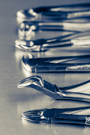 pincers: many old dental pincers - removers in a row on metalic background, blue duotone Stock Photo