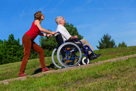 young woman push the old man on wheelchair to the top of the hill in the park Stock Photo