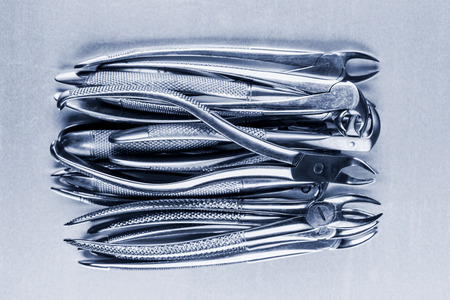 duotone: many old dental pincers - removers on the pile on metalic background, blue duotone