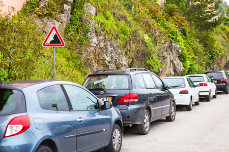 ignorance: Sintra, Portugal 2016 06 16 - cars standing near the road sign falling rocks and mountain - ignorance and danger