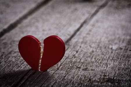 unfaithful: red broken heart on wooden background - dark and moody Stock Photo