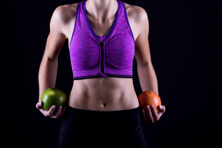athletic girl with fruits in hands on black background